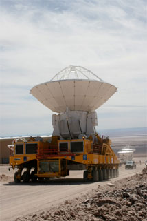 Figure 5: ALMA transporter Otto moves Melco antenna No 4 from the contractor area to the OSF Technical Building area.  Vertex Antennas No 2 and No 1 are also visible (background right).  This was the first move of an antenna by Otto, and the first move of a Melco antenna; the test before the AAER Committee went flawlessly.